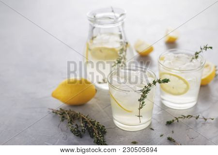 Homemade Thyme Lemonade With Ice In Glasses And In The Jug On The Stone Table. Summer Cold Refreshin