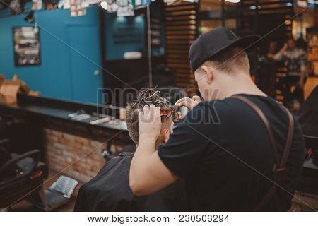 Barber Shop. Master Makes Haircut With Scissors And Comb To Man