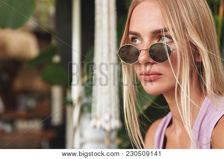 Sideways Portrait Of Thoughtful Stylish Hipster Girl In Trendy Sunglasses, Looks Pensively Away, Con
