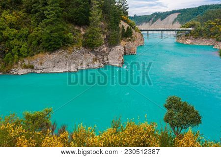 Bridge over river Rakaia with a view at  turquoise river and blooming yellow gorse