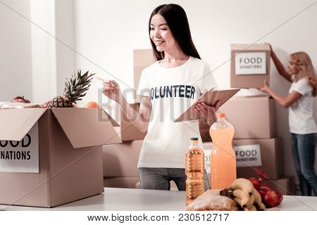 Want To Count. Positive Delighted Girl Keeping Smile On Her Face And Holding Folder In Left Hand Whi