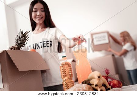 Put It Inside. Attractive Brunette Expressing Positivity While Packing Products And Doing Good Actio