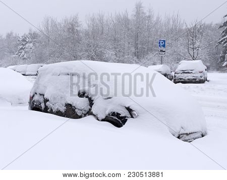 Vehicles Covered With Snow In The Winter Blizzard In The Parking.