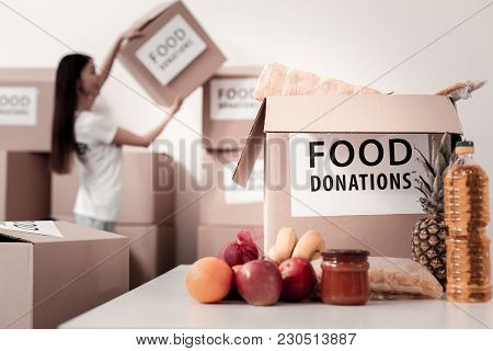 So Heavy. Focused Photo On Big Parcel That Standing On The Table, Fresh Fruits Lying Near It