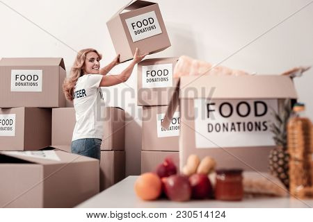 Facial Expressions. Pretty Young Female Turning Her Head While Looking At Camera, Holding Big Box