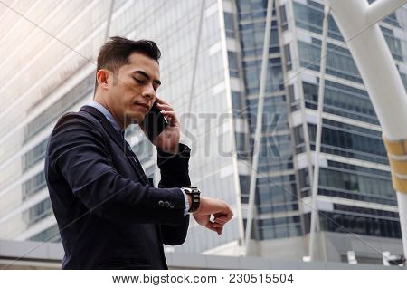 Young Smart Asian Business Man Wearing Modern Black Suit Looking At His Watch And Making Phone Call