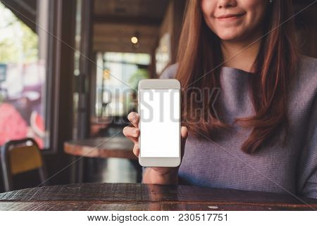 Mockup Image Of A Beautiful Asian Woman Holding And Showing White Mobile Phone With Blank Desktop Sc