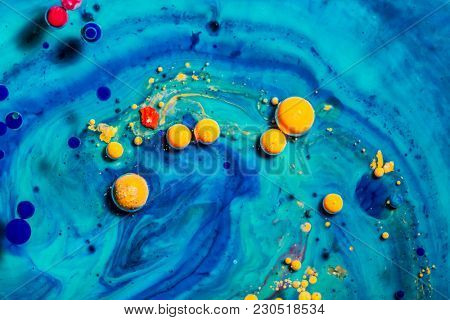 Yellow colorful bubbles in blue acrylic paint. Abstract colorful background