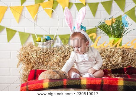 Cute Little Baby Wearing Bunny Ears On Easter Day And Stroking Rabbit; Happy Easter