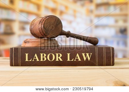 Labor Law books with a judges gavel on desk in the library. Law education ,law books concept. poster