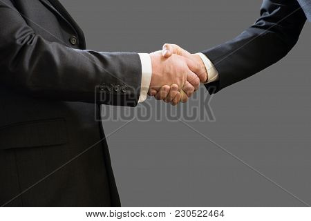 Business Handshake Of Two Businessmen In Suits Isolated On Grey Background.