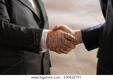 Business Handshake Of Two Businessmen In Suits, Negotiate And Make A Deal.