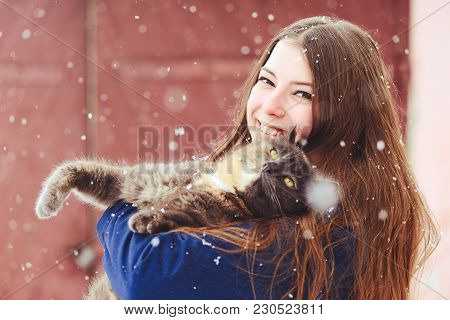 Winter Portrait Of A Young Woman With A Cat. Beauty Joyous Model A Girl Laughs And Is Happy To Have