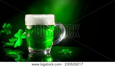 St. Patric's Day Green Beer pint over dark green background, decorated with shamrock leaves. Patric Day pub party, celebrating. Mug of Green beer close-up. Traditional Irish festival. Border art