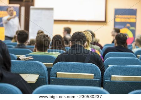 Male Presenter Holding A Conference In Front Of A Group Of Listeneres. In A Congress Hall. Horizonta