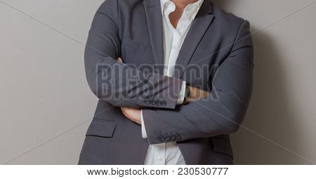 Close Up Cropped Caucasian Man Hands And Arms Folded In A Smart Grey Suit