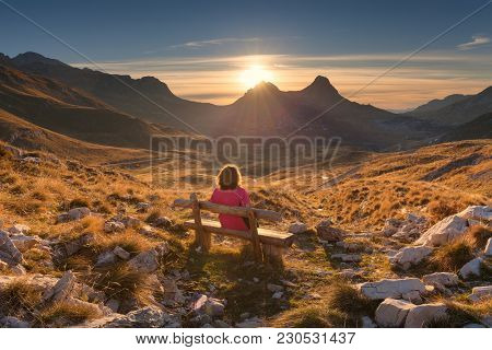 Lone Woman Sitting On The Wooden Bench And Watching Beautiful Mountain Scenery At Idyllic Sunrise. D