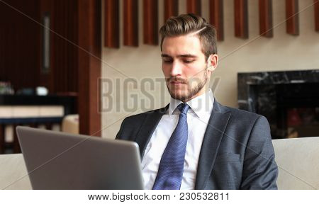 Young Businessman Working On Laptop, Sitting In Hotel Lobby Waiting For Someone