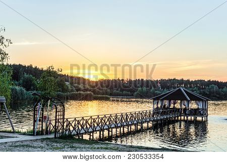 Footbridge With A Gazebo On The Lake Shore In Light Of The Low Evening Sun. Sunset And Quiet Holiday