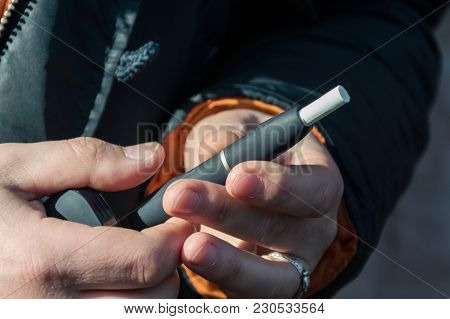 A Heat-not-burn Tobacco Product Technology. Man Holding In Two Hands Smoking Module Before Smoking.