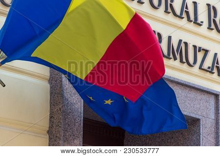 Flags Of The Romania And European Union Waving In The Breeze On The Wall Of Building
