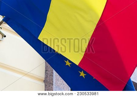 Close-up View Of The Waving Flags Of The Romania And European Union. Flag Of The Eu Is Hidden With R