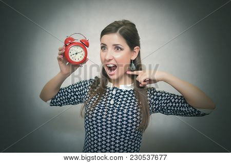 Angry Woman Holding In Hands A Red Alarm Clock And Showing On It By Her Finger And Shouting. Wicked