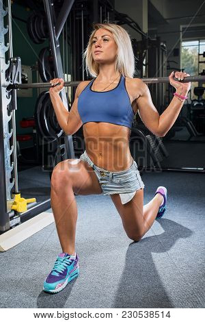 Fit Girl Doing Lunges With The Smith Machine In The Gym In A Denim Shorts And Blue Top