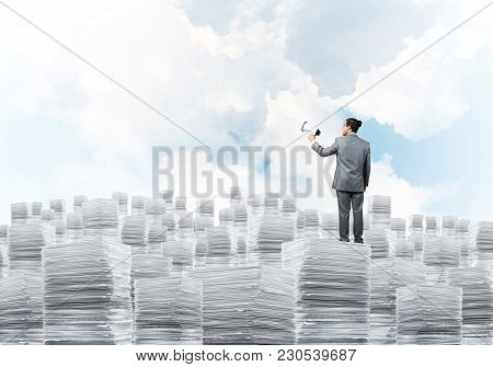 Businessman In Suit Standing On Pile Of Documents With Speaker In Hand With Cloudly Skyscape On Back