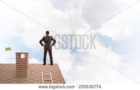 Young Determined Businessman Standing With Back On House Roof And Looking Away. Mixed Media