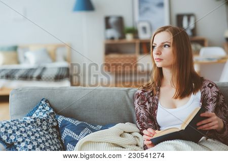 Indoor Lifestyle Portrait Of Young Woman Relaxing At Home With Cup Of Hot Tea Or Coffee, Sitting On