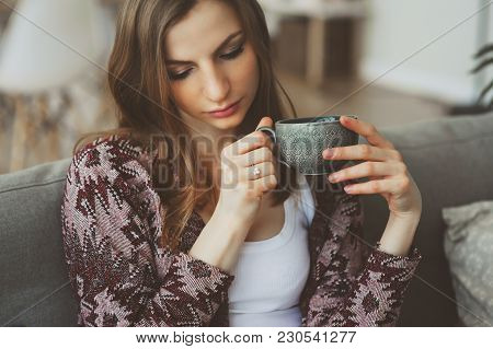 Close Up Portrait Of Young Thoughtful Woman With Cup Of Tea Or Coffee Sitting Alone At Home. Depress