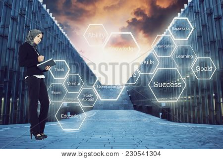 Beautiful Confident Student Standing And Holding Book Over Abstract Word Cloud Backgound