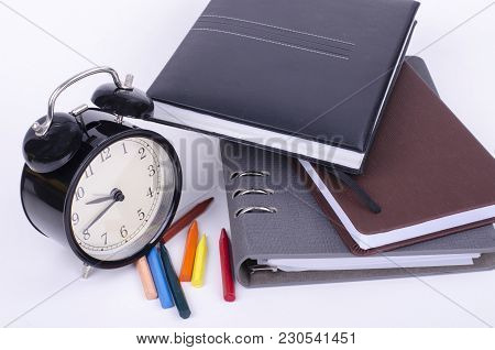 Stack Of Book With Ticking Vintage Clock, And Colorful Crayon On White Table.