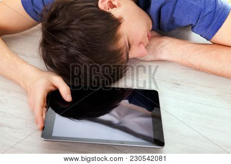 Young Man Sleep On The Table With A Tablet Computer