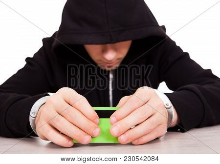 Sad Person In Handcuffs With A Bank Card On The Table Closeup