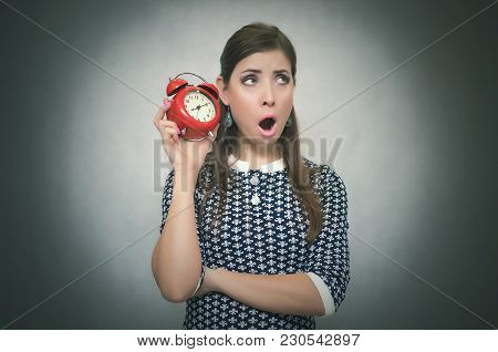 Sleepy Woman Holding In Hands Alarm Clock And Looking Aside. Latecomer Student Or Emloyee. Be Late A