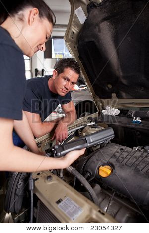 A team of mechanics using an electronic diagnostics tool