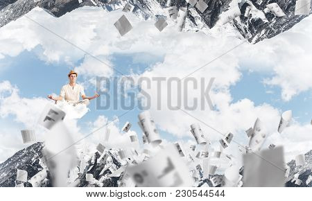 Young Man Keeping Eyes Closed And Looking Concentrated While Meditating On Cloud Among Flying Papers
