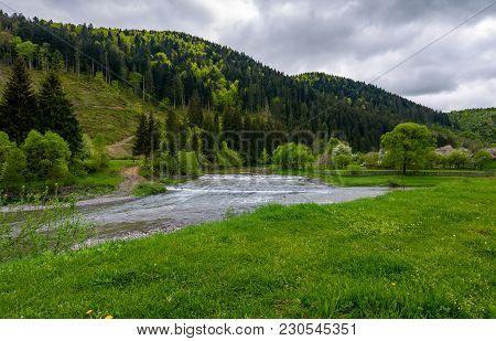 Lovely Village Outskirts On The River Bank At The Foot Of The Forested Mountain. Lovely Countryside