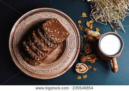 Dark Cereal Bread With Sunflower Seeds, On A Plate, Scalded Nuts, Cup Of Milk, Raisins On Shale Boar
