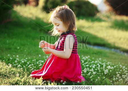Cute Girl In Red Dress Collects Wildflowers. Happy Baby In A Good Mood. Allergy To Pollen.