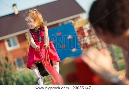 Happy Child On Seesaw. Joyfil Little Girl At Playground. Active Games With Children On The Street.