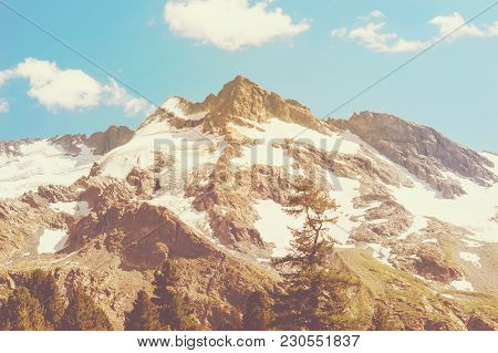 Picturesque Amplitudinous Prospect Of Mountains In Sunlight. Tinted Photo. The Snowy Peak On The Bac