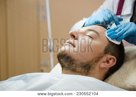 Doctor Aesthetician Makes Hyaluronic Acid Rejuvenation Beauty Injections In The Forehead Of Male Pat