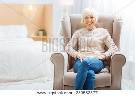 Comfort. Cute Pleasant Aged Lady Feeling Good While Being Alone In A Beautiful Light Room And Sittin