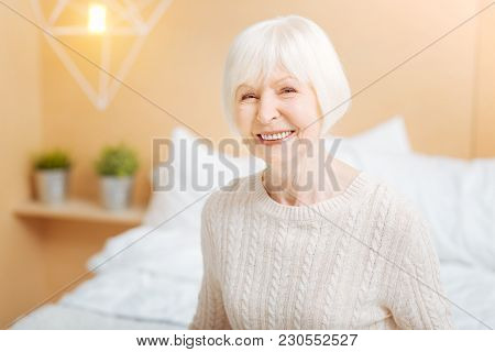 Kind Smile. Pretty Cute Positive Elderly Lady Looking Adorable And Feeling Happy While Being At Home