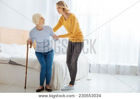 So Weak. Calm Attentive Caring Woman Supporting Her Aged Worried Grandmother While Looking At Her An