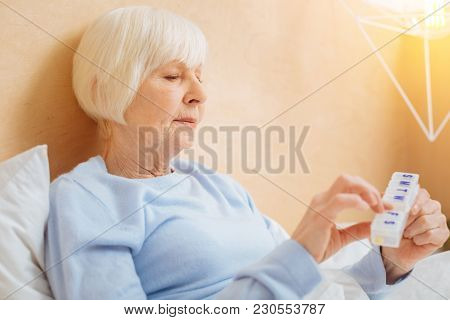 This One. Calm Thoughtful Ill Elderly Woman Staying In Bed And Carefully Looking At The Tiny Pillbox