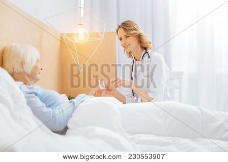 Kind Doctor. Pleasant Kind Cheerful Polite Doctor Looking Friendly While Smiling To Her Aged Ill Pat